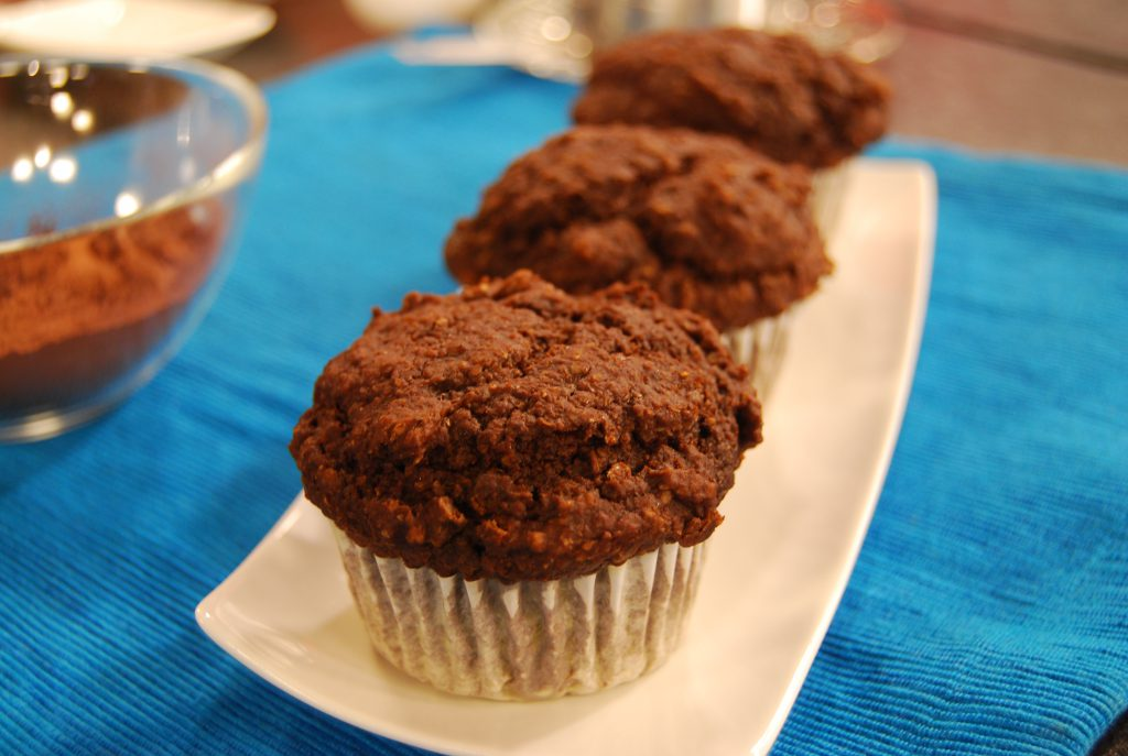 three chocolate muffins sitting on a white plate