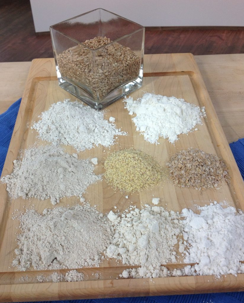 types of wheat and flour on a wooden board