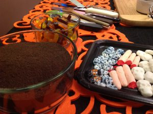 Chocolate cookie crumbs for the dirt, gummy worms, skeletons and candy fingers!