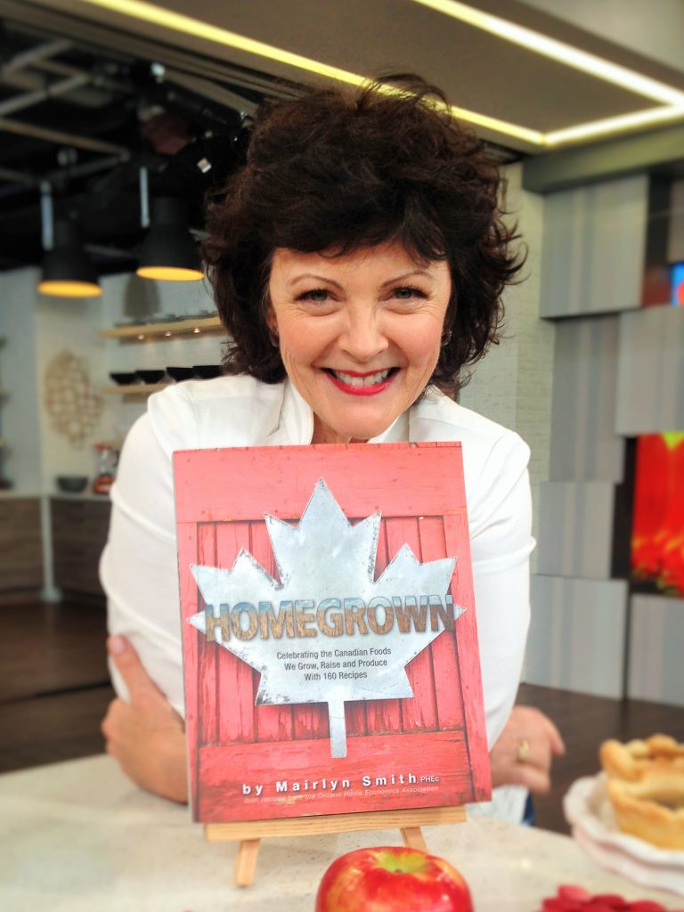 Mairlyn Smith standing behind a copy of Homegrown