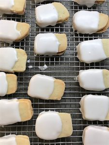 Shortbread Empire cookies on a rack as the almond icing sets