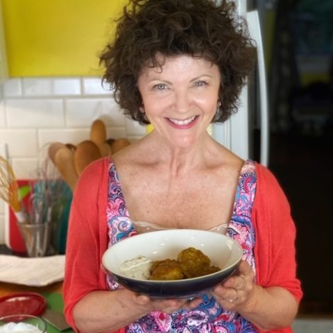 holding a plate of chicken with rhubarb in a curry sauce