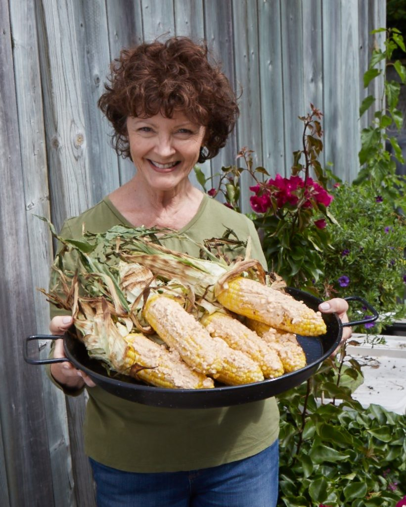 mairlyn is holding a platter of grilled corn